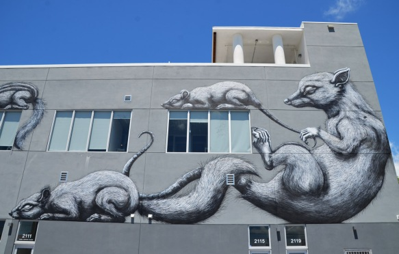 a large black and white mural on a grey building, by ROA, two adult animals and two babies