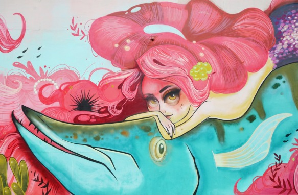 pink haired mermaid resting on top of a blue fish, mural