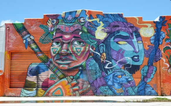 large mural, upper part of two people, one has face painted