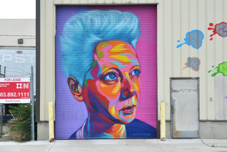 Denver street art mural of a woman's face on a large door. bright blue hair, background is pink and purple, skin in oranges, yellows and blues, by Detour303