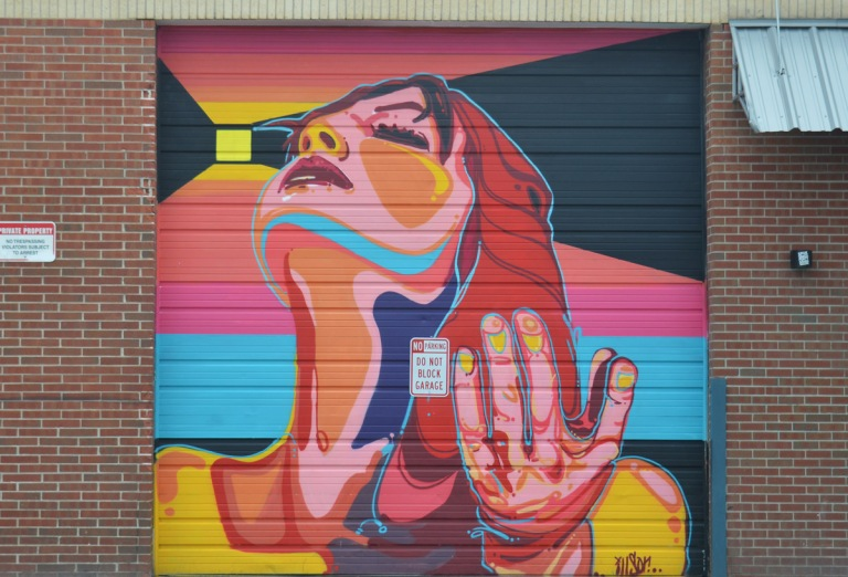 colourful mural on a garage door by illson in denver of a woman looking upward, with one of her hands raised up a bit