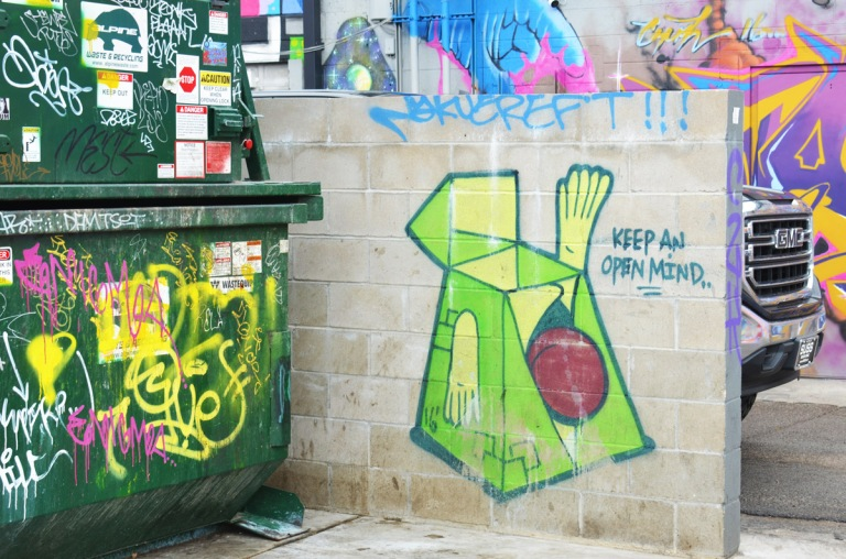 Denver street art on a small, low concrete wall of a green figure with the words keep an open mind. a graffiti covered garbage skip is beside it.