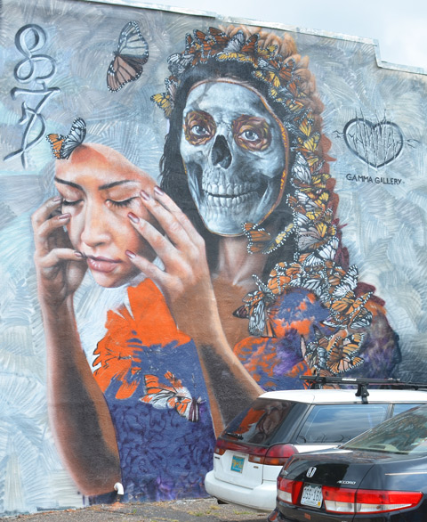 Denver street art mural of a woman with long hair that is actually butterflies, by Gamma Gallery. She has her face in hands, like a mask, revealing her skull below. Very large, two storeys high