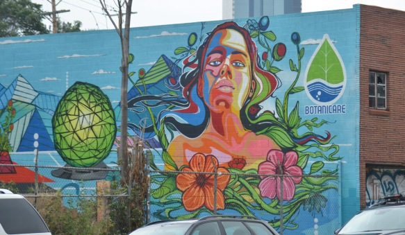 part mural and part ad for botanicare products, a woman in many colours with long flowing hair, two large hibiscus flowers in front of her, on the side of a building in Denver