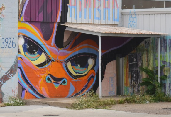 on a wall on Blake St in Denver, a face in oranges and purples partially behind an overhang porch over a door a