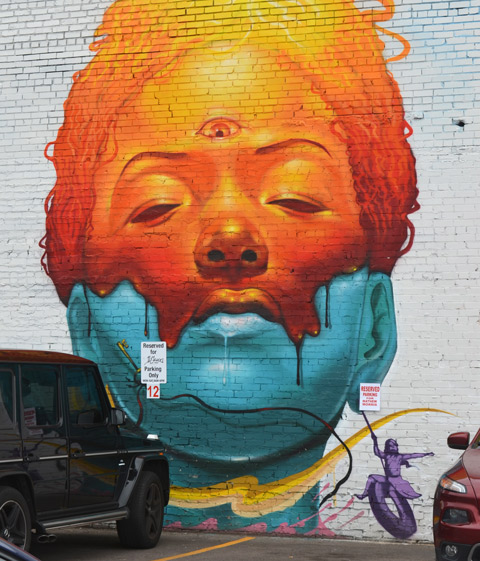Denver street art mural of a woman's head, top part is orange and bottom is blue, the orange part is melting into the blue. eyes closed. From the cheek, in purple, a small tire swing with a small girl playing on it.