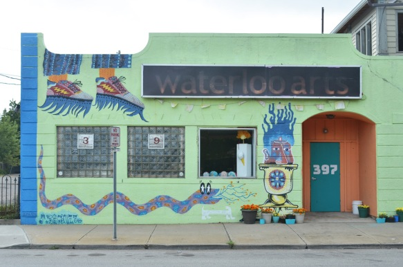 the front of the Waterloo Arts building in Cleveland, painted in light green with other designs, such as a long snake. three windows, two are closed and one is open