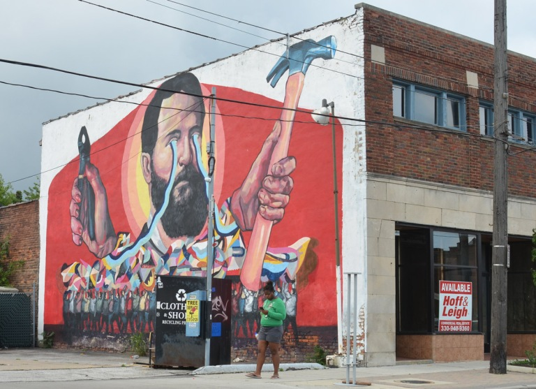 a woman walks past a building with a large mural painted on it, a man holds a hammer in one hand and a pair of pliers in the other, blue lines loop from his eyes to the tools, old store front is empty, Cleveland,