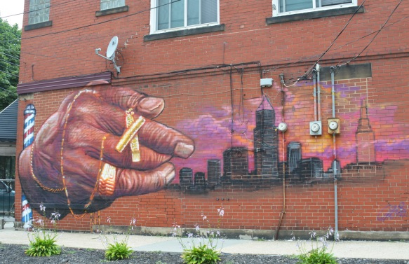 mural on side of red brick building on Waterloo Road in Cleveland, a large hand with rings and bracelets is reaching towards a cityscape in black with pink yellow and orange sky