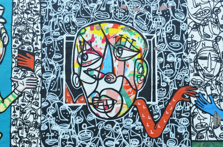 close up of a mural with face in many colours, all drawn with lines, long red arm reaches in one direction, background is black and white faces