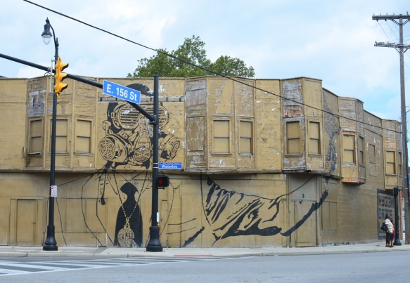 very large mural in black on a boarded up goldish coloured building, windows painted same colour as building, two storeys, man in a gas mask, at the corner of 156th Street and Waterloo in Cleveland