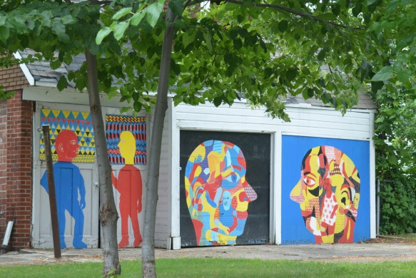 double car garage with a face painted on each, one with black background and the other with blue background, big multi coloured faces that are looking at each other, beside the garage is a fence and gate with two more figures painted on them, one red with a yellow head and the other is blue with a red head