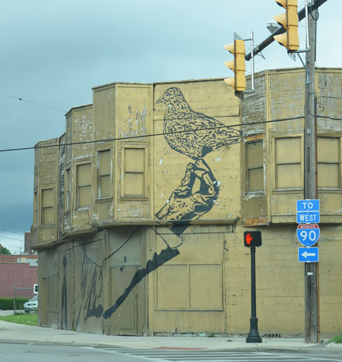 continuation of mural of man in gas mask, building is on a corner and the mural exte4nds around the corner, there is a large bird in his hand,