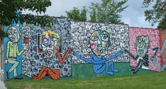 four panels in a a mural of people with large multicoloured faces, blue and red bodies, all holding hands,