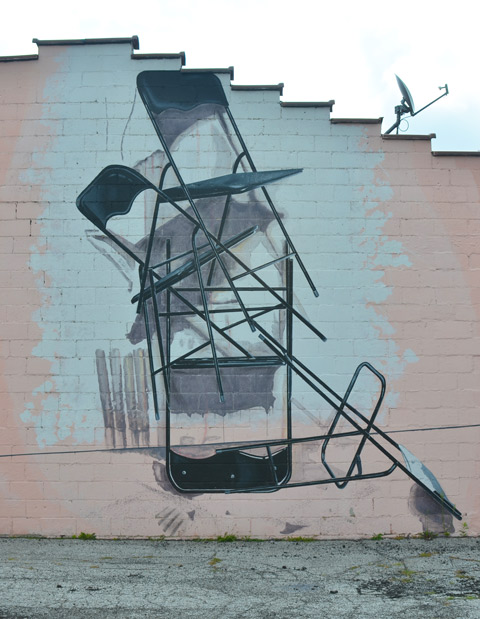 on the side of building in CLeveland, a mural of a stack of foldable chairs, open, disorderly pile, not neatly piled,