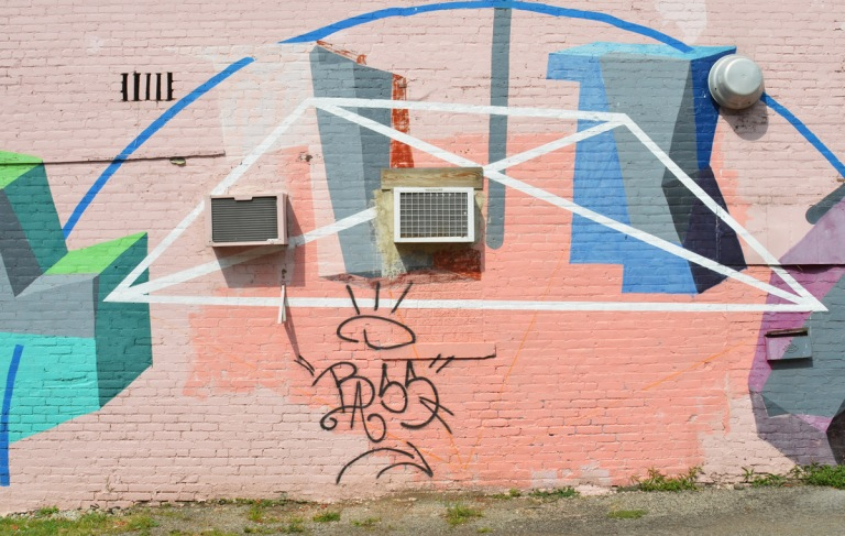 abstract geometric shapes in a mural, pink background, shapes in blues and greys along with some blue and white lines