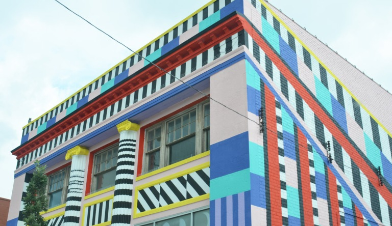 upper part of a building that has been painted in stripes and rectangles of colours including black and white sections