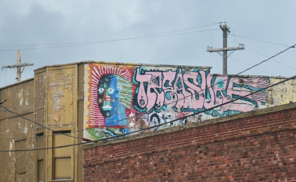 Cleveland street art, exterior, on the upper level of a building, face in many colours, with text that says treasure