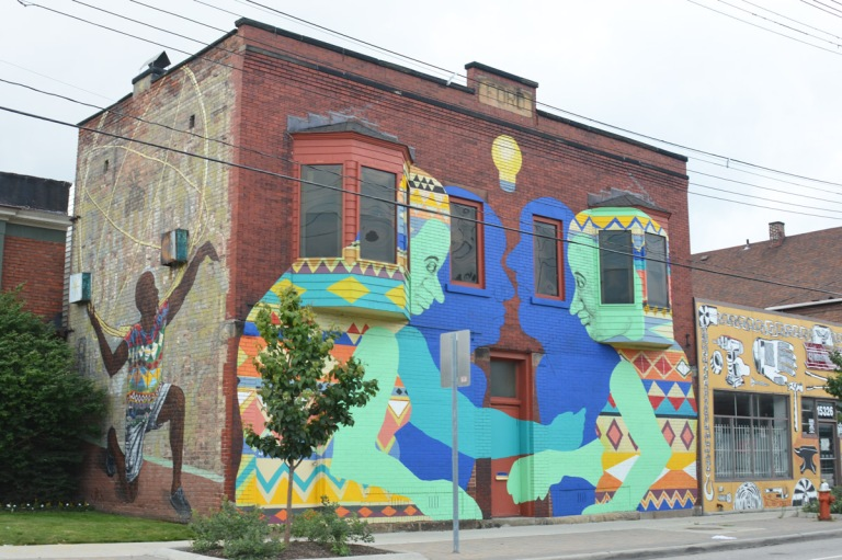 street art murals on two sides of a two storey building, on side is a black person dancing and on the front are two older people that are facing each other, takes up whole front of the building, there is a blue shadow for each that represents their younger selves.
