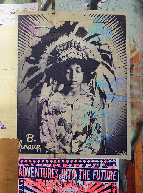 be brave pasteup by donk, ofLondon, in Bristol a young person with eys closed, Indian feather head dress on hed, in monotone black and white