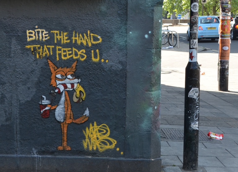 a graffiti fox, standing on two legs, with words, bite the hand that feeds you.
