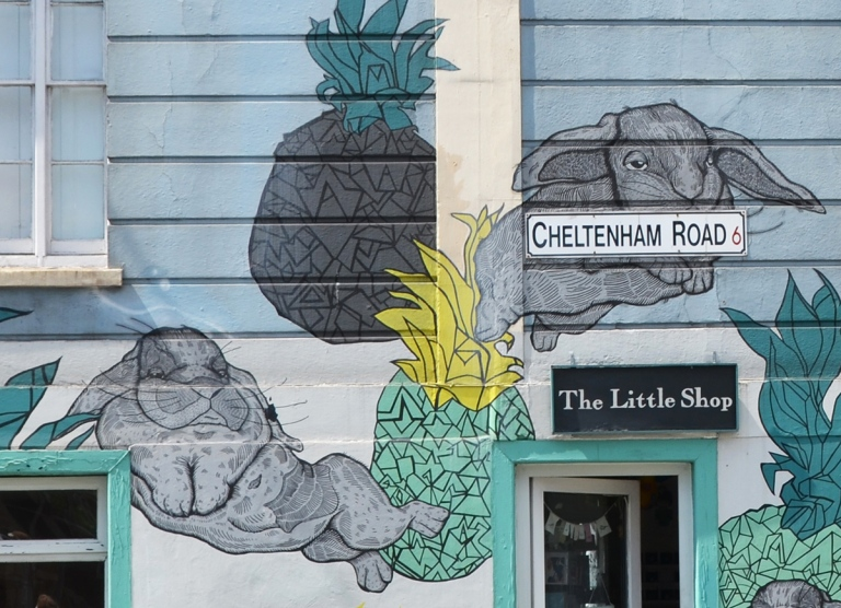 close up of mural - bunny rabbits and pineapples on a blue store frnt, The LIttle Shop on Cheltenham ROad in Bristol