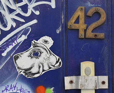 on a blue door with the number 2 on it, a small black and white paste of a head of a creature, signed creature [illegible name - maybe arequte?]