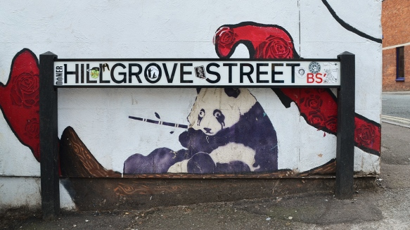 small street art piece of a panda with bamboo in its mouth, under a street sign for Hillgrove Street