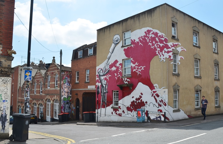 buildings on a street in Bristol, including one with a large mural by phlegm,large red and white wave with a person on a ladder besideit looking through a telescope