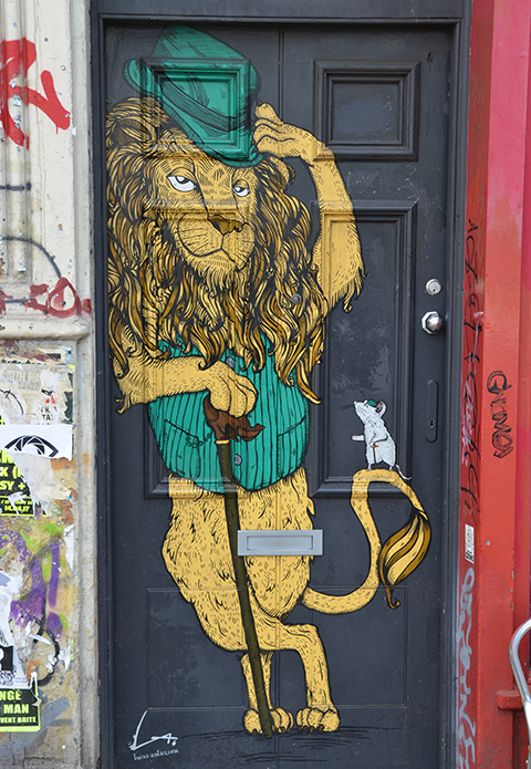 a lion standing in a doorway, by lucas_antics, green vest and green hat, holding a cane, tail curled up and a white mouse on the tail