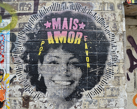 pasteup of a smiling woman's head, large puffy hairdo, words say mais amor por favor.