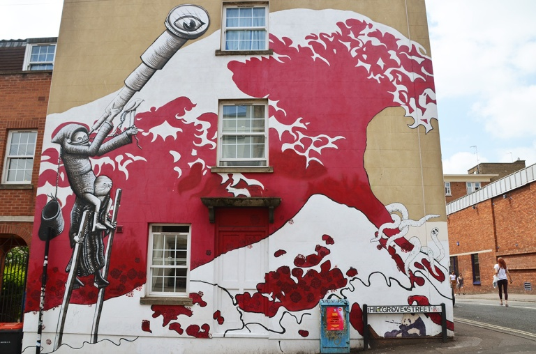 large mural by phlegm,large red and white wave with a person on a ladder besideit looking through a telescope