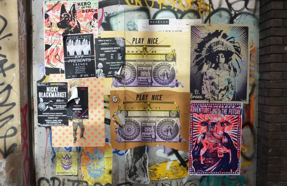 section of wall covered with pasteups, be brave, play nice, adventures into the future, hero of the beach dog, ghetto blaster