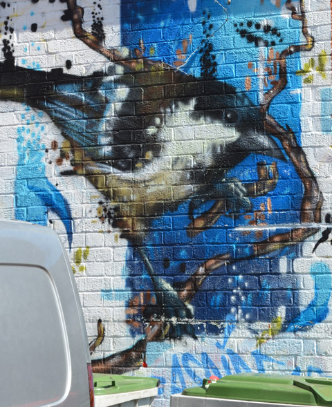 street art mural of a bird, blue and grey and black