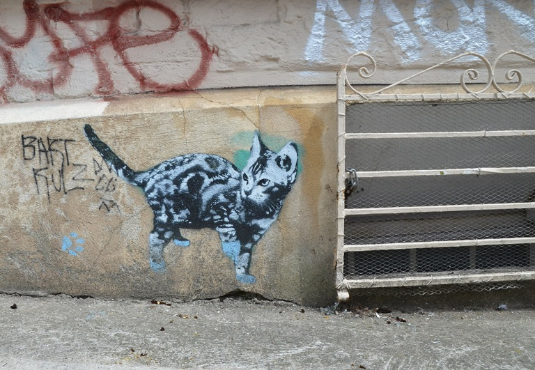 small stencil of a realistic looking cat, on a concrete wall, at sidewalk level so itloks like it's walking on the pavement