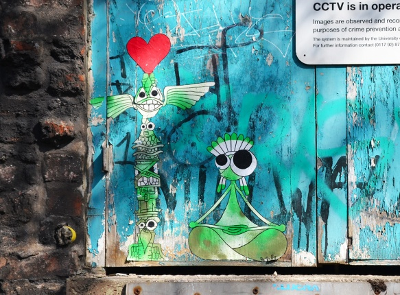 two little green andwhite characters on a blue wall, a red heart is above the head of a tall skinny standing creature while the other is sitting crossed legged beside him