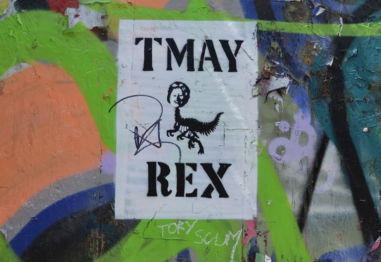 black and white poster on a graffiti spray painted wall, words n poster say TMay Rex with a picture in the middle of May's (British Prime Minister) head on a dinosaur