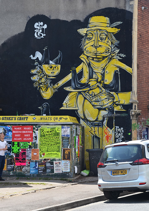 mural, yellow and grey on black background, car parked in front. Mural is a man holding a tea cup in one hand.