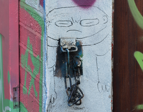 small drawing on a wall, man with scowling face, large head and small body,