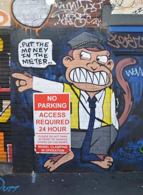 parking meter man as a monkey, sneering, and pointing, beside a sign that says no parking, words on street art say put the oney in the meter
