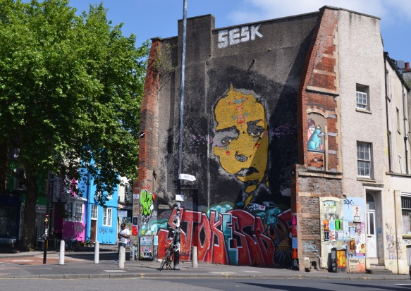 large mural of a yellow woman's face, long black hair, on the side of a building, blue and red text graffiti along the bottom