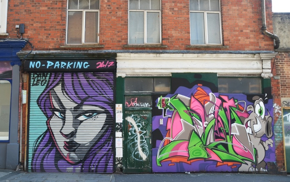 street art, 3 pieces,painting of woman's head in grey and purple, graffiti in pink and green shapes, plus drawing on a door in the middle