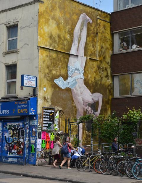 large mural of a man upside down on one hand, only a loincloth on, no other clothes