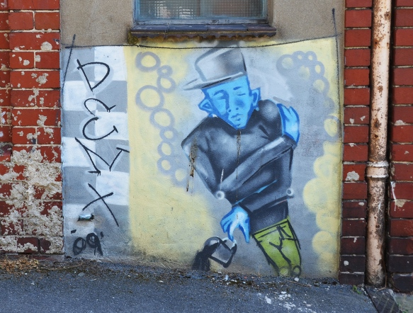 street art painting of a man with blue face, black hat and jacket and green pants