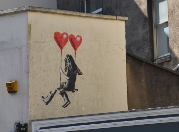 street art piece of s girl sitting on a swing that is being held up by two red balloons