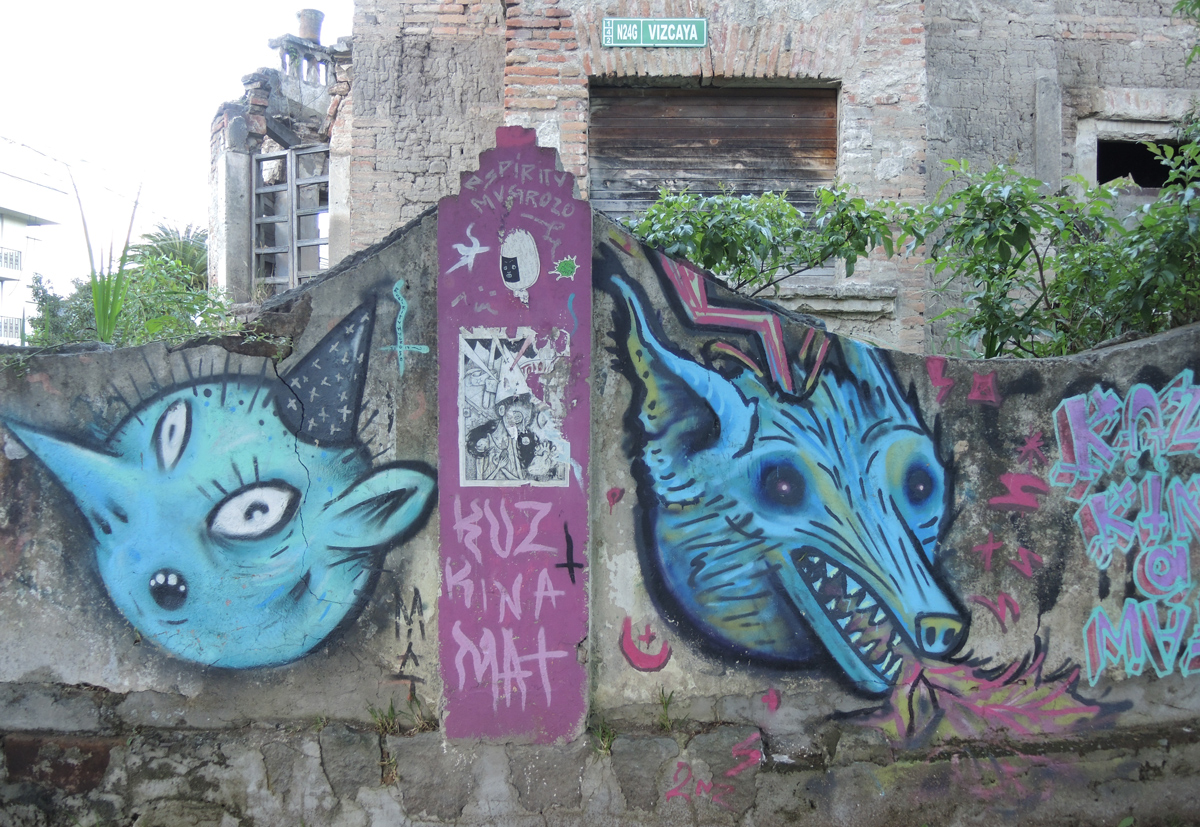 on an old stone wall, two animal heads, a dog and a cat maybe.