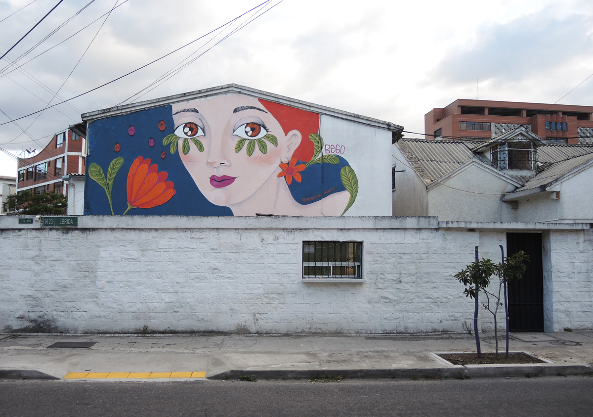 on a house beyond a white fence, a painting on the upper storey of a woman with red hair and red flower