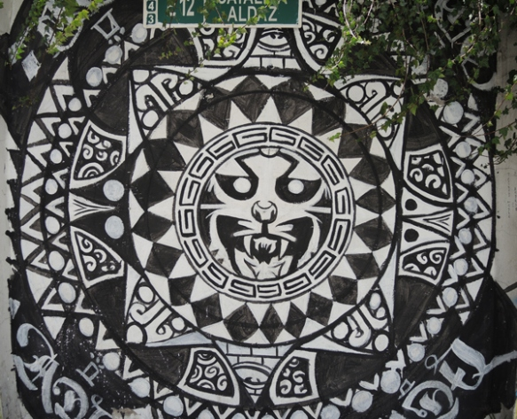 circular pattern painted in black and white with a cat's face ferocious in the center circle, painted mural