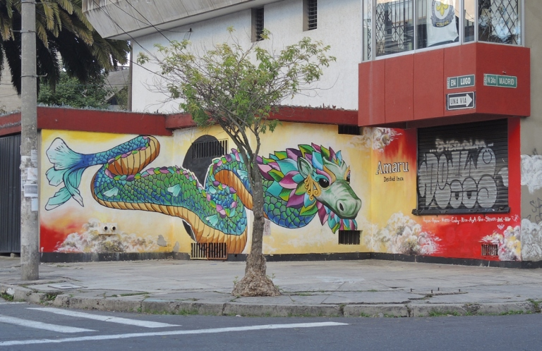 on a yellow wall, behind a small tree, a colourful painting of a dragon