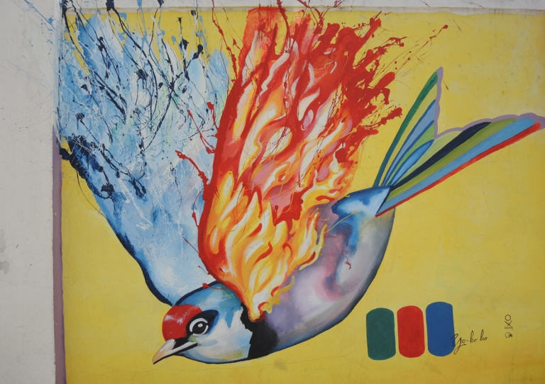 street art in Quito Ecuador, a bird in flight, one wing looks like flames and the other wing looks like water, painted by yo_ho_ho. mural in Quito Ecuador